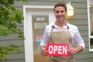 """Small Business owner with """"open"""" sign"""